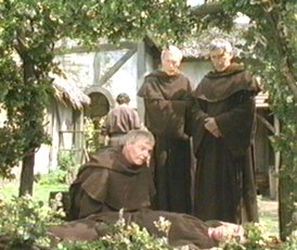 Brother Cadfael examines the body of the monk sent to pay the Rose Rent